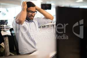 Tensed businessman clenching teeth in office