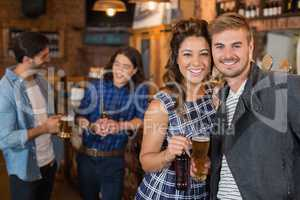 Smiling friends holding beer glass and bottle in pub
