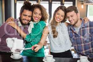 Friends taking selfie while enjoying in restaurant