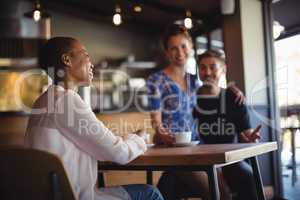 Friend interacting with happy couple while having coffee