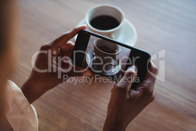 Hands of woman taking a clicking picture of black coffee
