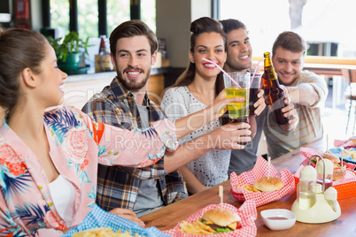 Cheerful friends enjoying beer with food at restaurant