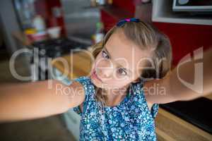 Girl pulling funny faces in kitchen