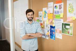 Portrait of young smiling businessman with arms crossed by soft board at office