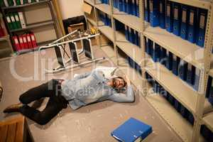 High angle view of fallen businessman and file in storage room