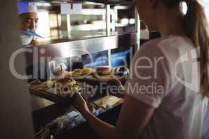 Chef passing tray with french fries and burger to waitress