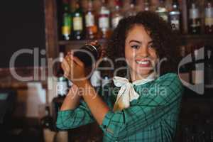 Portrait of female bartender mixing a cocktail drink in cocktail shaker