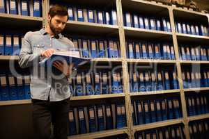 Concerned businessman reading file in storage room