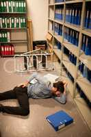 Fallen businessman with file in storage room