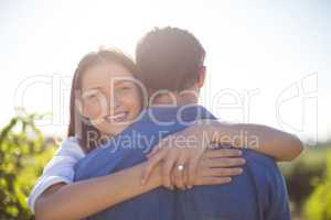 Happy woman hugging her boyfriend during sunny day