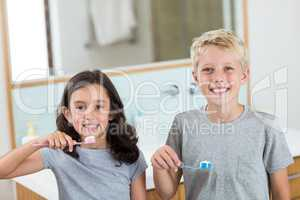 Siblings brushing their teeth in bathroom