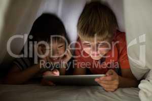 Siblings under bed sheet using digital tablet on bed