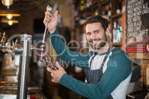 Portrait of bartender pouring beer from tap