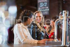 Smiling females standing by bar counter