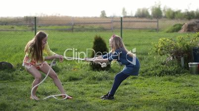 Joyful family playing tug of war in yard outdoors