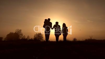 Family silhouettes on spirng sunset in the meadow