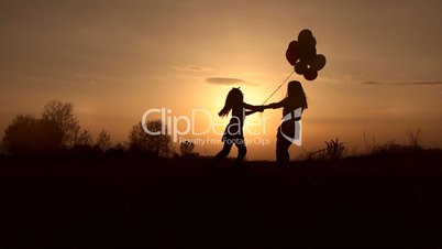 Mother and daughter playing in field at sunset