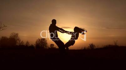Couple in love whirling on the meadow at sunset