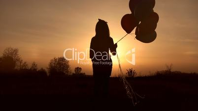 Girl walking with balloons in field at sunset.