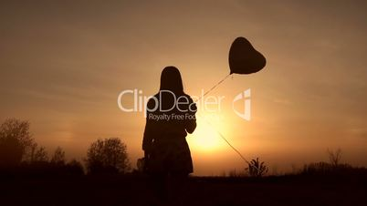 Silhouette of young woman with balloon at sunset