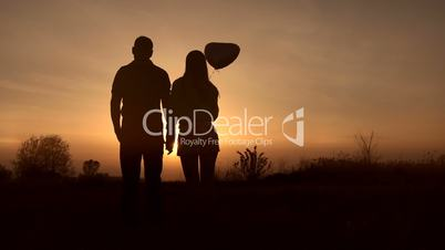 Romantic couple in love watching beautiful sunset