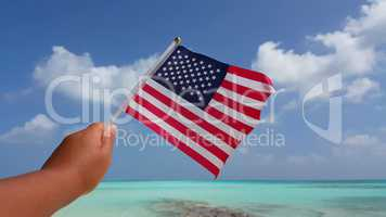 v01099 Maldives beautiful beach background white sandy tropical paradise island with blue sky sea water ocean 4k hand holding us american flag
