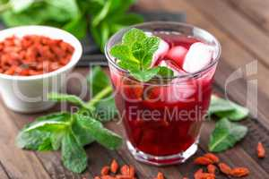 Healthy detox drink with goji berries infused in water with ice, cold refreshing beverage
