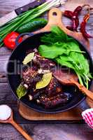 Cooked in spices pork ribs on a black cast-iron frying pan