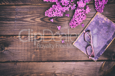 Aold book in the cover and glasses in a frame on a brown surface