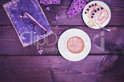 Coffee in a white cup with a saucer and a biscuit cake on a wood