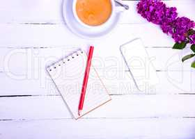 Empty little notebook with a red pencil and a mobile phone on a