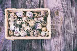 Raw quail eggs in a wicker basket, top view