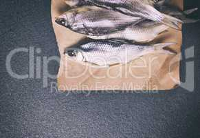 whole dried fish in the roach scales lying on brown paper