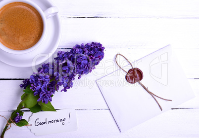sealed letter on a white wooden surface, near a lilac bud and a
