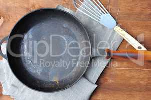 Empty black cast-iron frying pan and iron spatula on the table