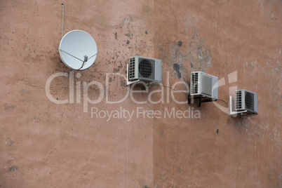 Three air conditioner on old building wall and satelite antena