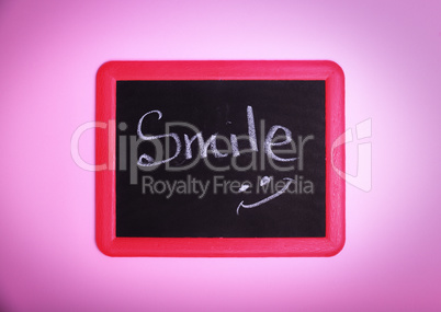 Chalkboard with an inscription smile on a pink surface