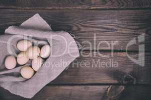 Fresh chicken eggs in shell lie on cloth gray napkin
