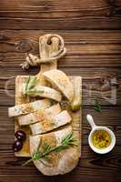 Delicious homemade italian ciabatta bread with olive oil and olives on wooden rustic background, above view