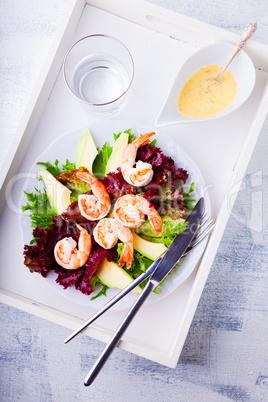 Avocado shrimp salad with mustard sauce on a tray