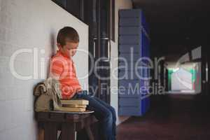 Sad boy sitting on bench by wall in corridor