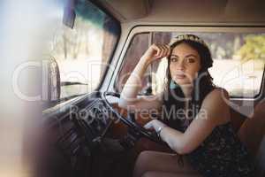 Portrait of beautiful woman leaning on steering wheel