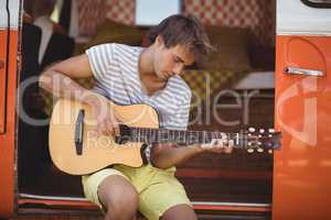 Young man playing guitar while sitting in motor home