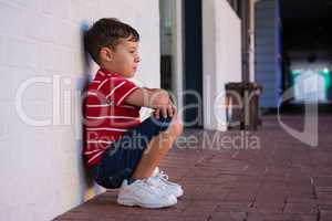 Side view of boy crouching by wall