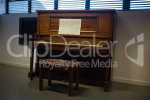 Wooden piano against window in clasroom