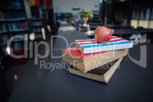 Apple on stack of books in liabrary
