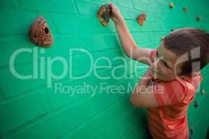 Elementary boy climbing on brick wall