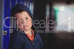 Portrait of sad boy leaning on locker