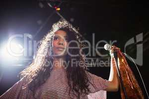 Thougthful young female singer holding mic at nightclub