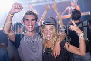 Portrait of cheerful friends with arm around at nightclub